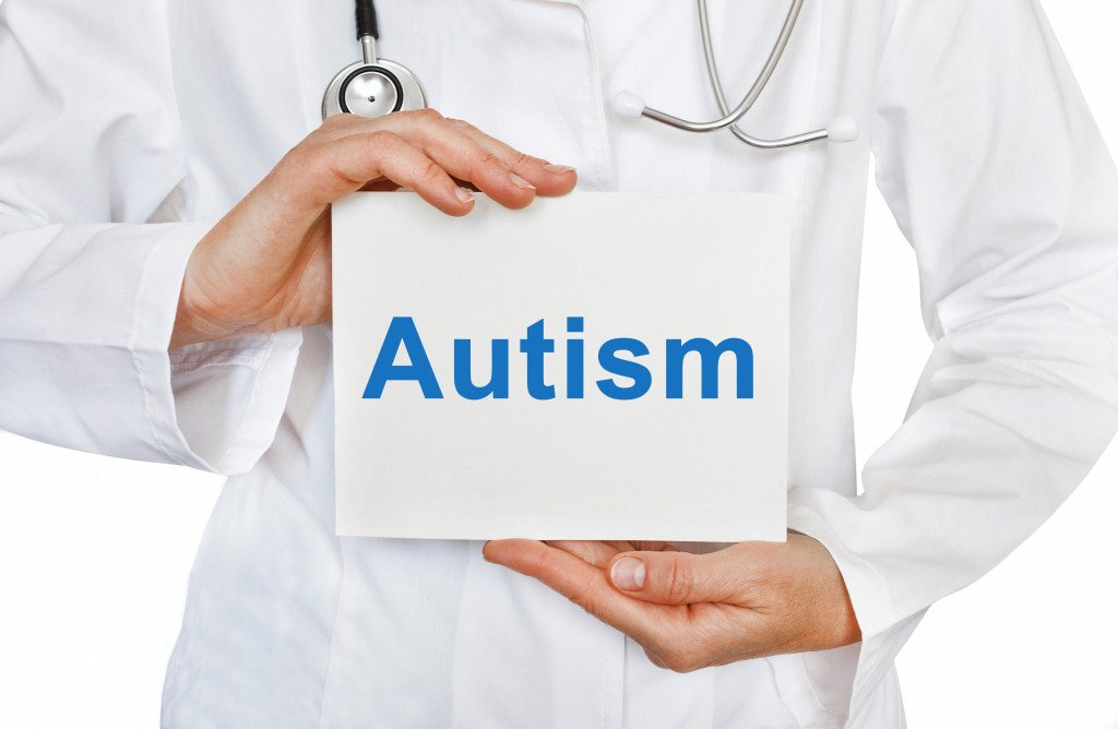 Doctor holding a card with Autism, Medical concept